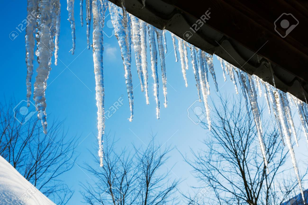 spring landscape with ice icicles hanging from roof of house.