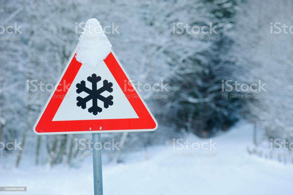 traffic sign warns of snow and ice at road